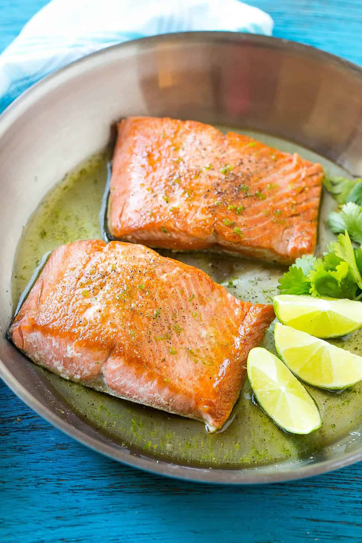 Two glazed salmon fillets in a pan with lime wedges and cilantro