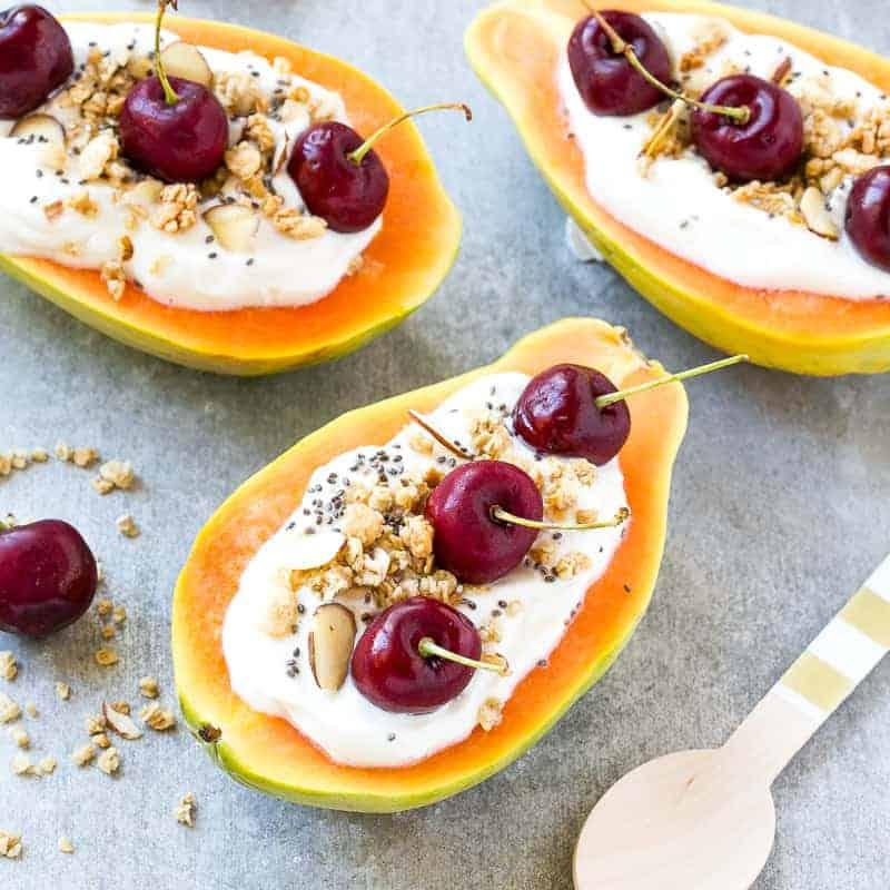 papaya topped with yogurt and cherries
