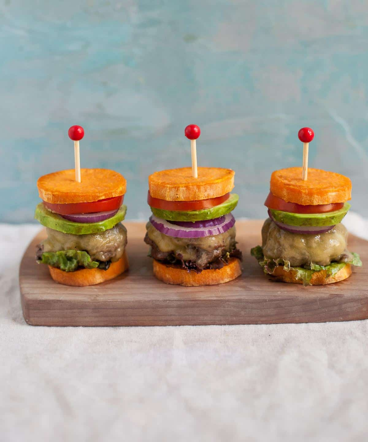 side view of 3 burger sliders on a board