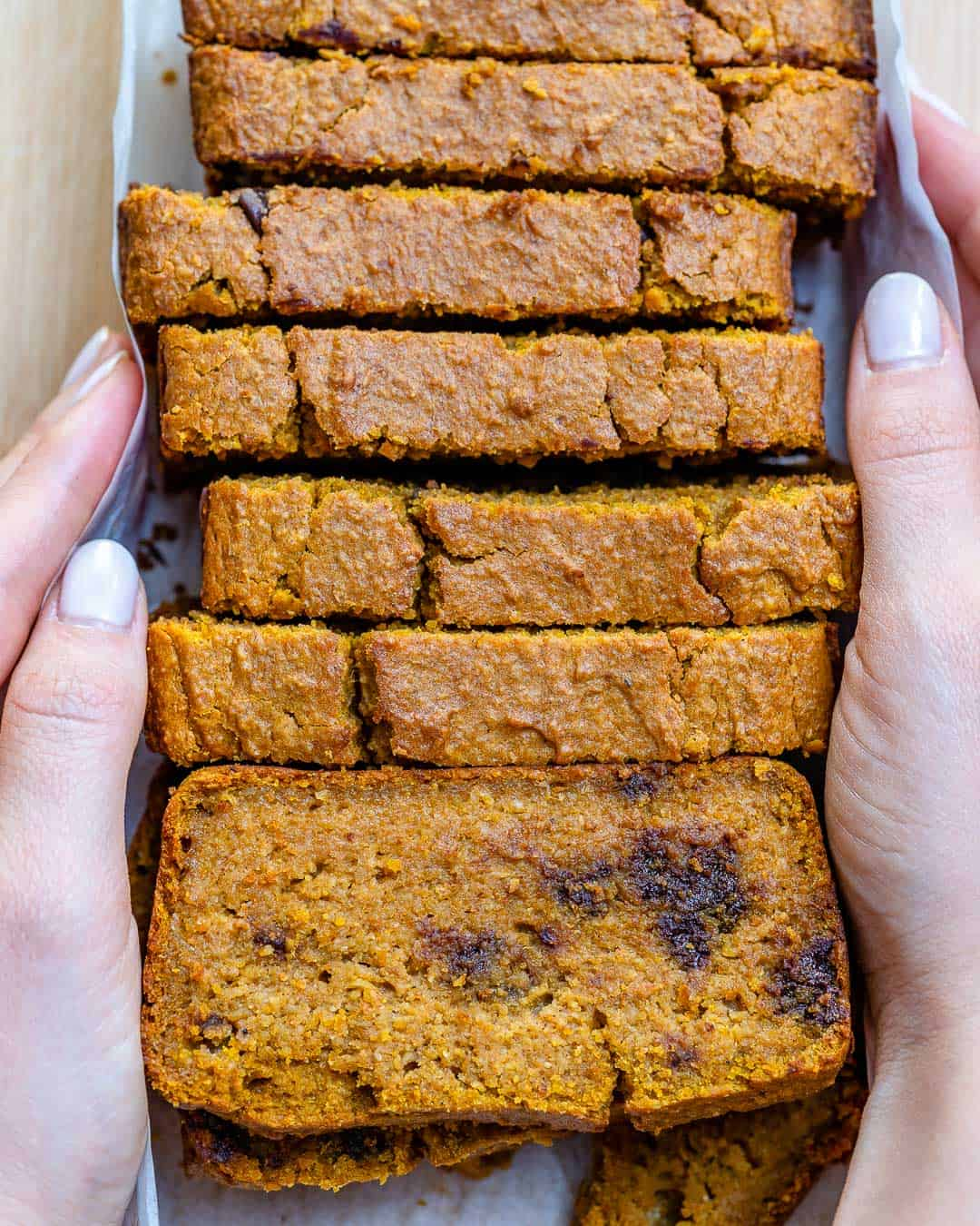 hand holding slices of pumpkin bread