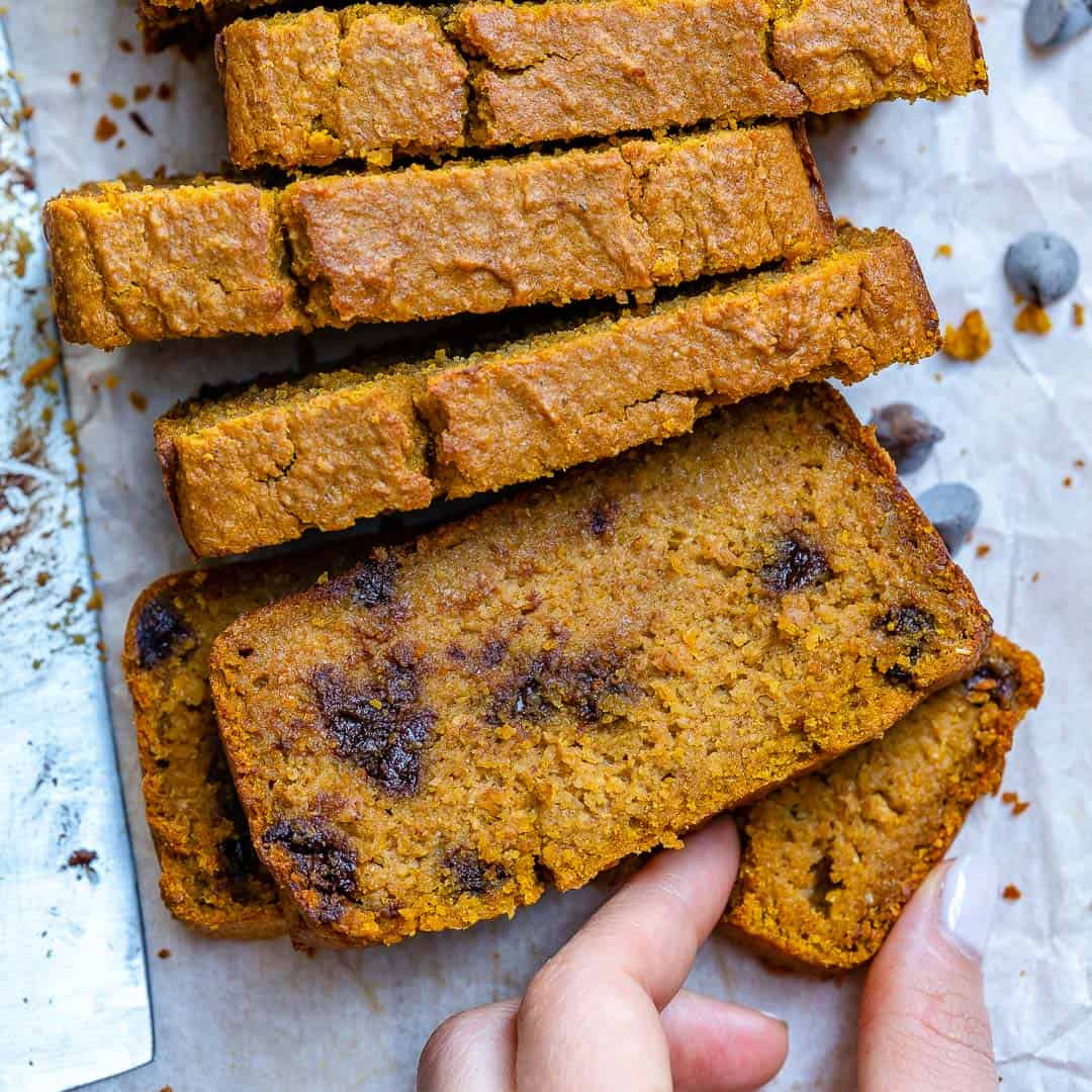 hand reaching to grab a slice of pumpkin bread