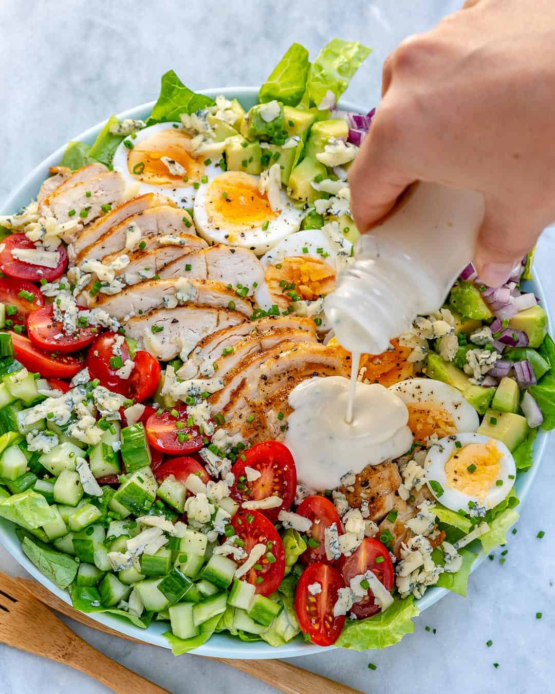 Grilled chicken Cobb salad with dressing being poured over salad