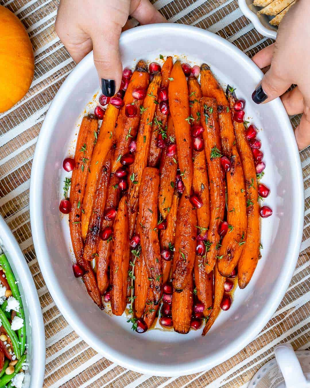 hand holding a dish of Roasted Carrots