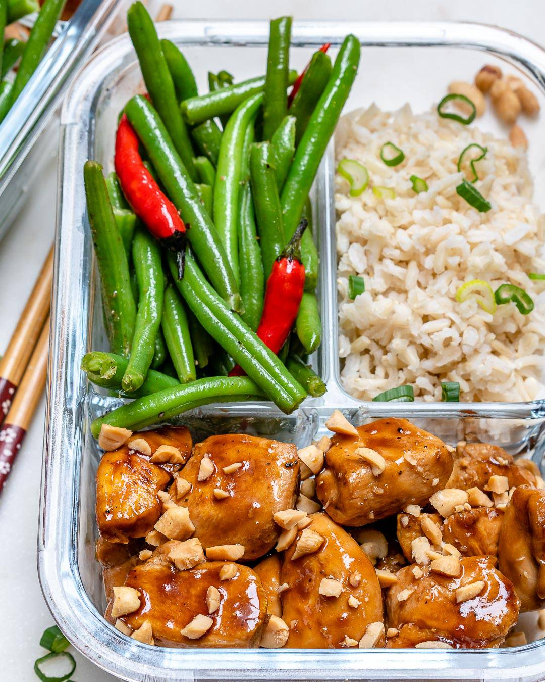Kung pao chicken in a glass container with beans and rice.