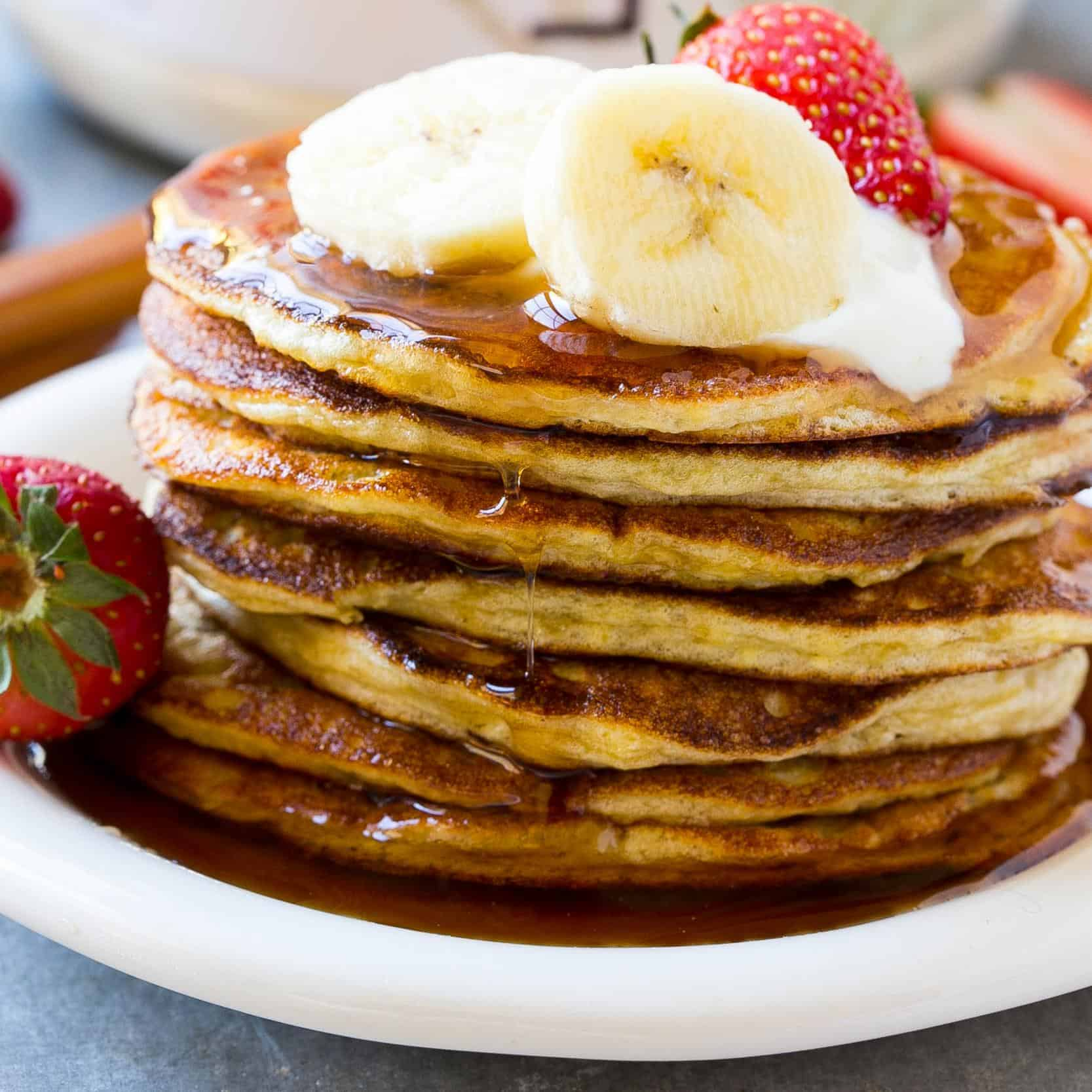 pancakes stacked on plate garnished with syrup