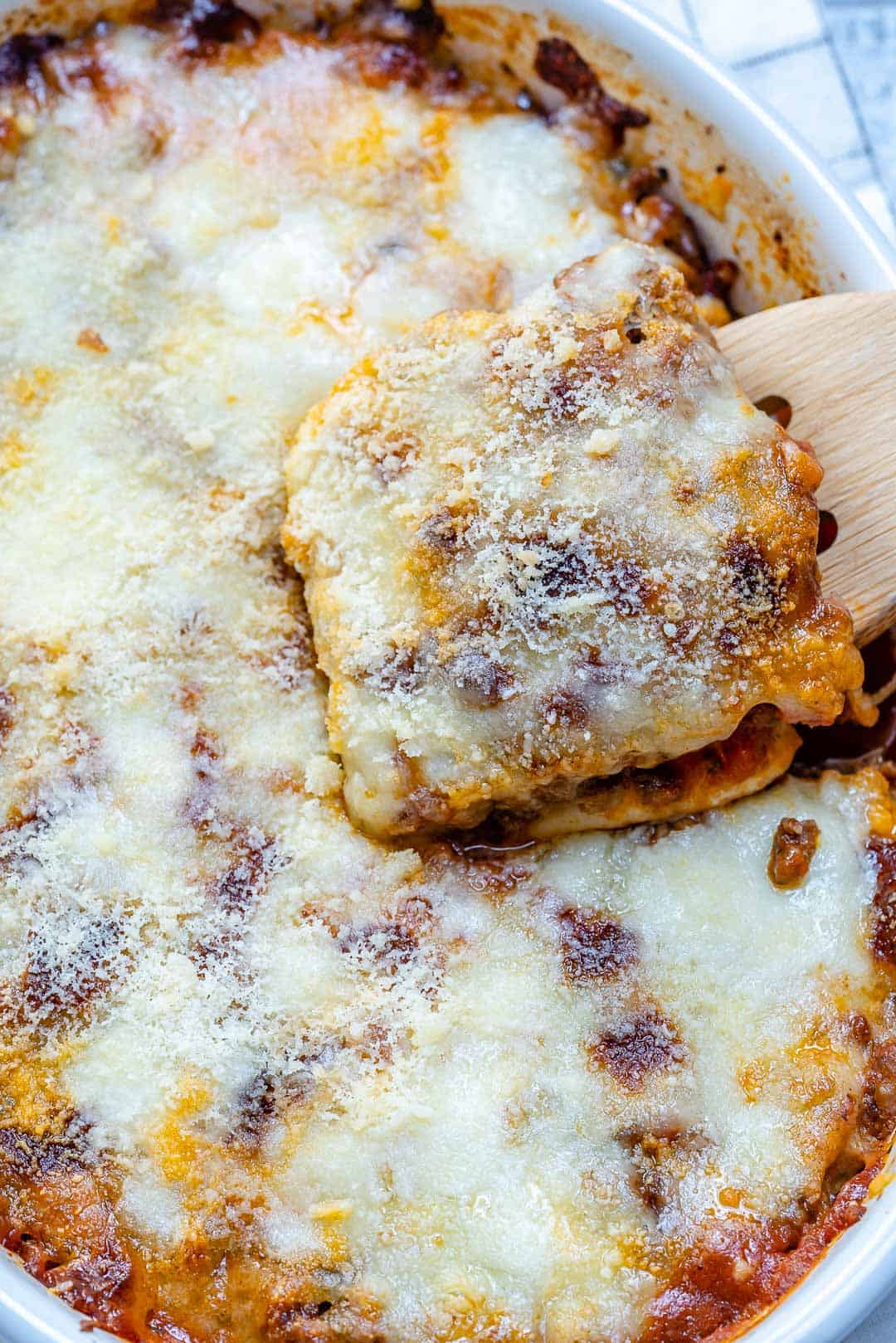 easy healthy lasagna in a dish with wooden spoon