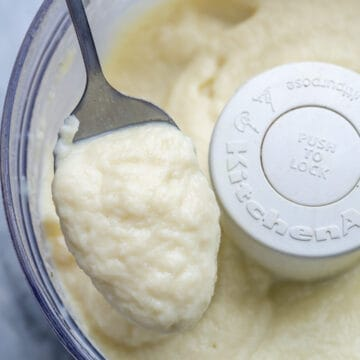 blended cauliflower sauce in food processor with a spoonful of the sauce