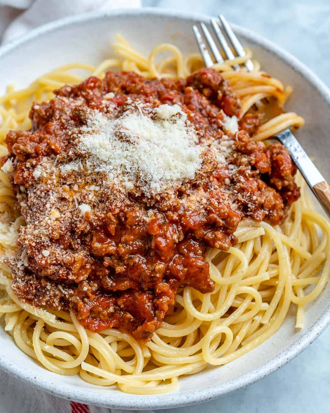 Homemade Meat Sauce served over cooked spaghetti with parmesan cheese on top