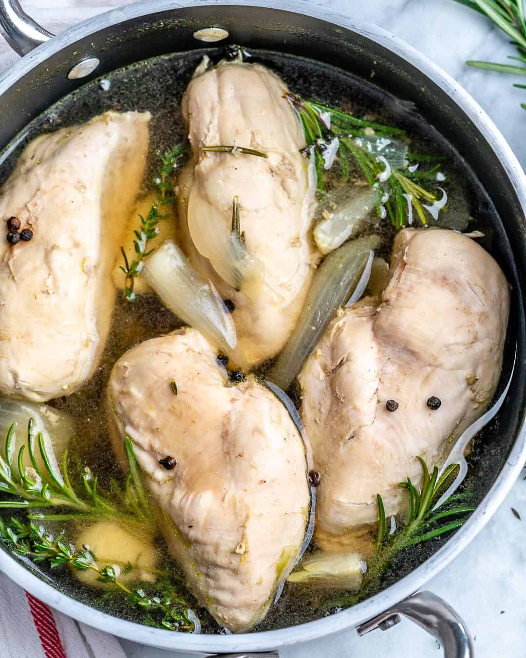 Poached chicken in pot with broth and herbs