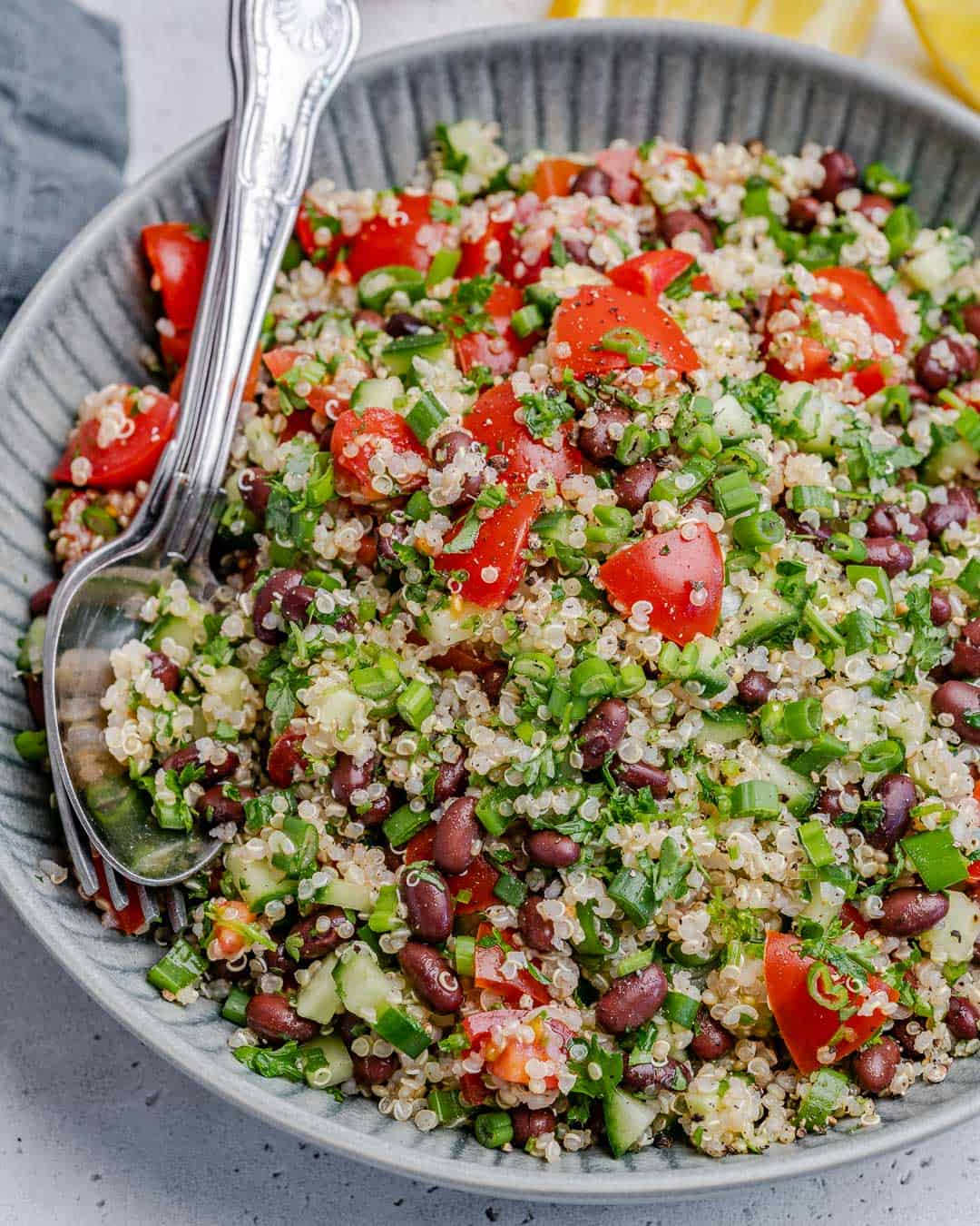 top view of mixed tabbouleh salad on a plate with spoon and fork in it