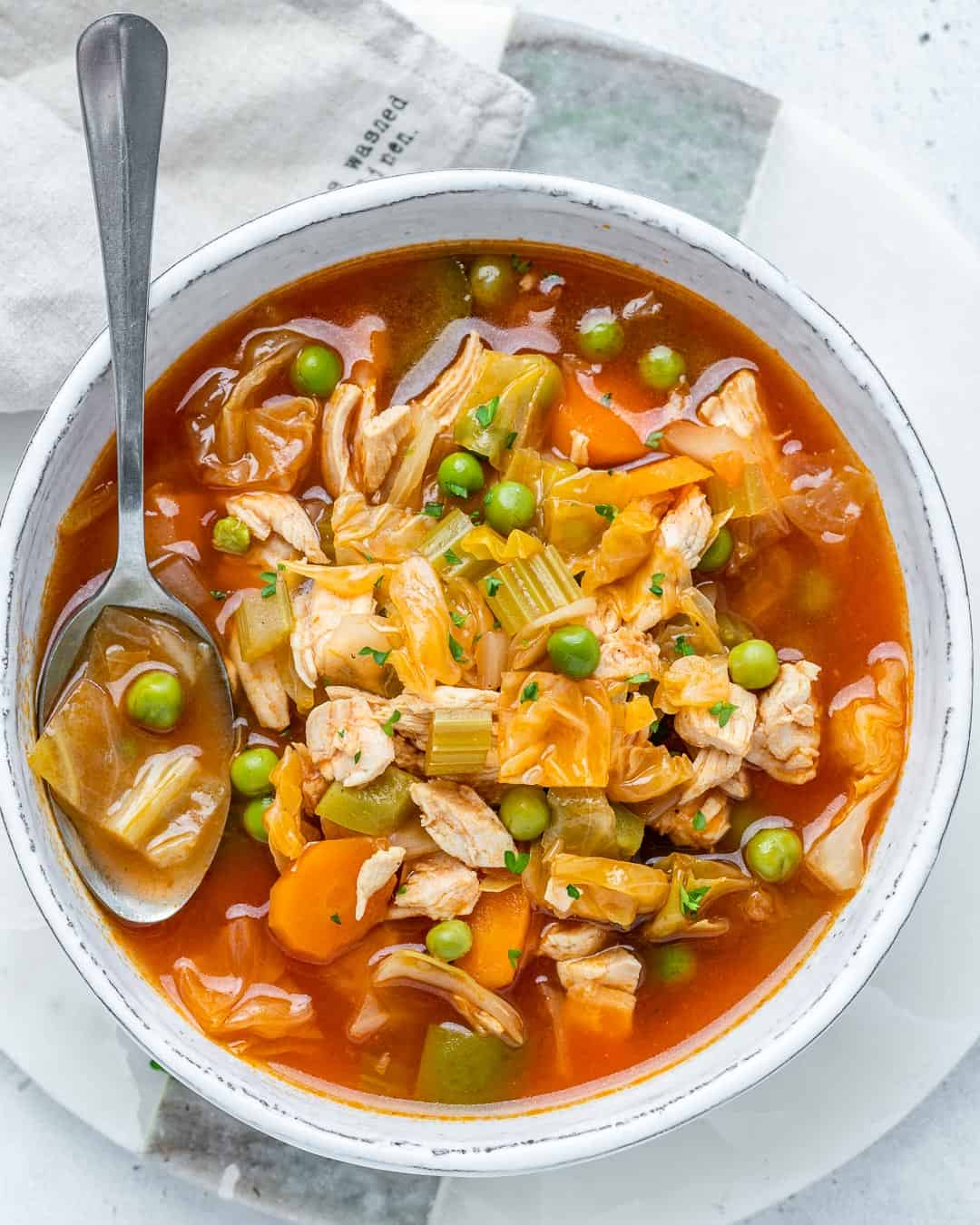 healthy chicken and veggie soup with spoon in bowl