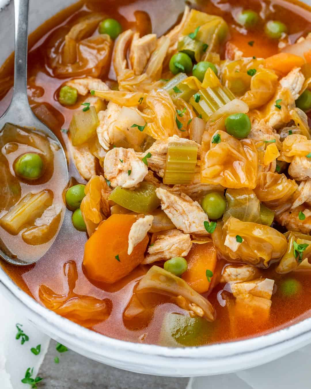 chicken and vegetable soup with cabbage, carrots, and peas