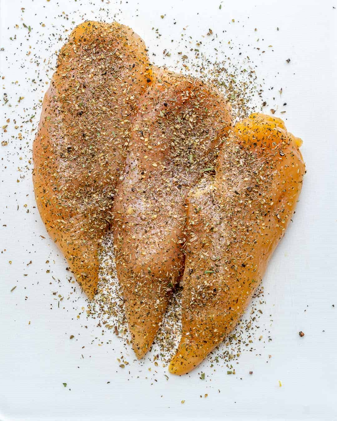 raw chicken breasts with seasoning