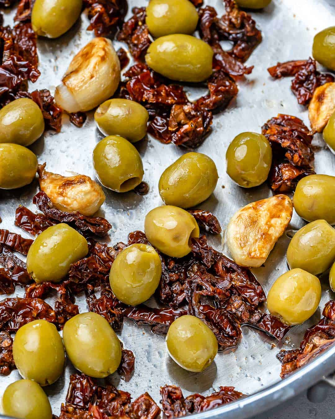 olives and sun dried tomatoes in pan with garlic