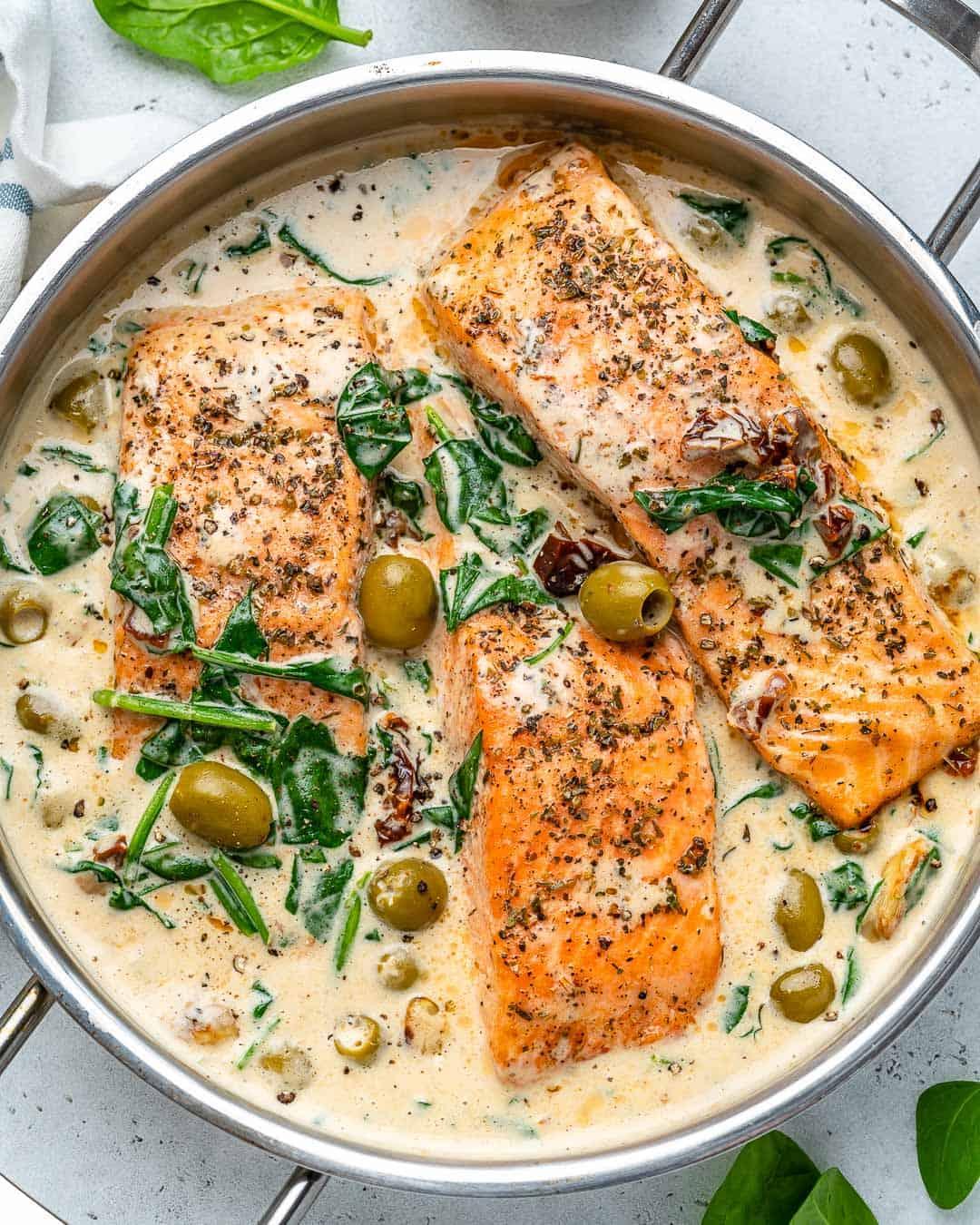 creamy pan-seared salmon in a pan with olive garnish