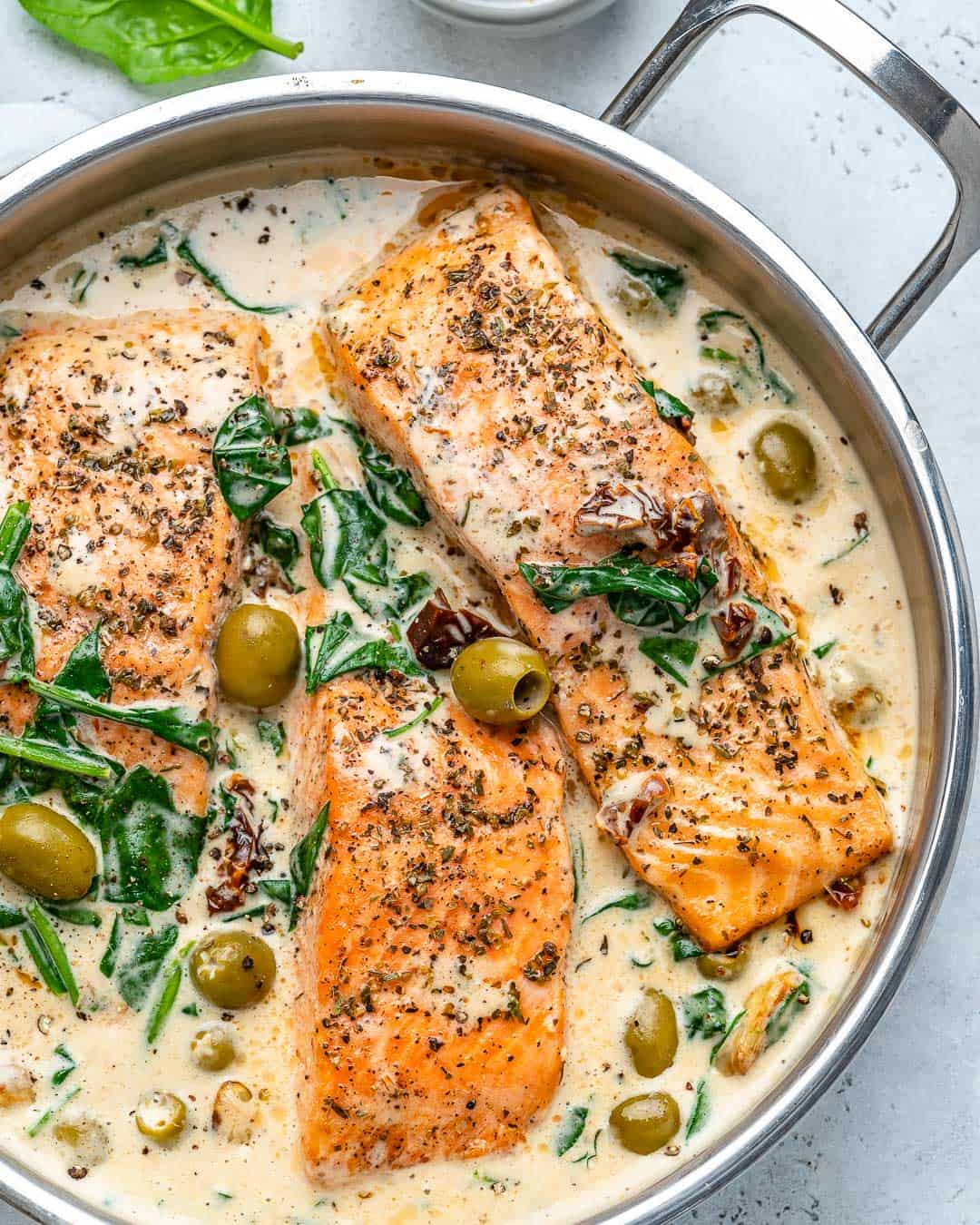 three salmon fillets in a pan with creamy sauce and olives