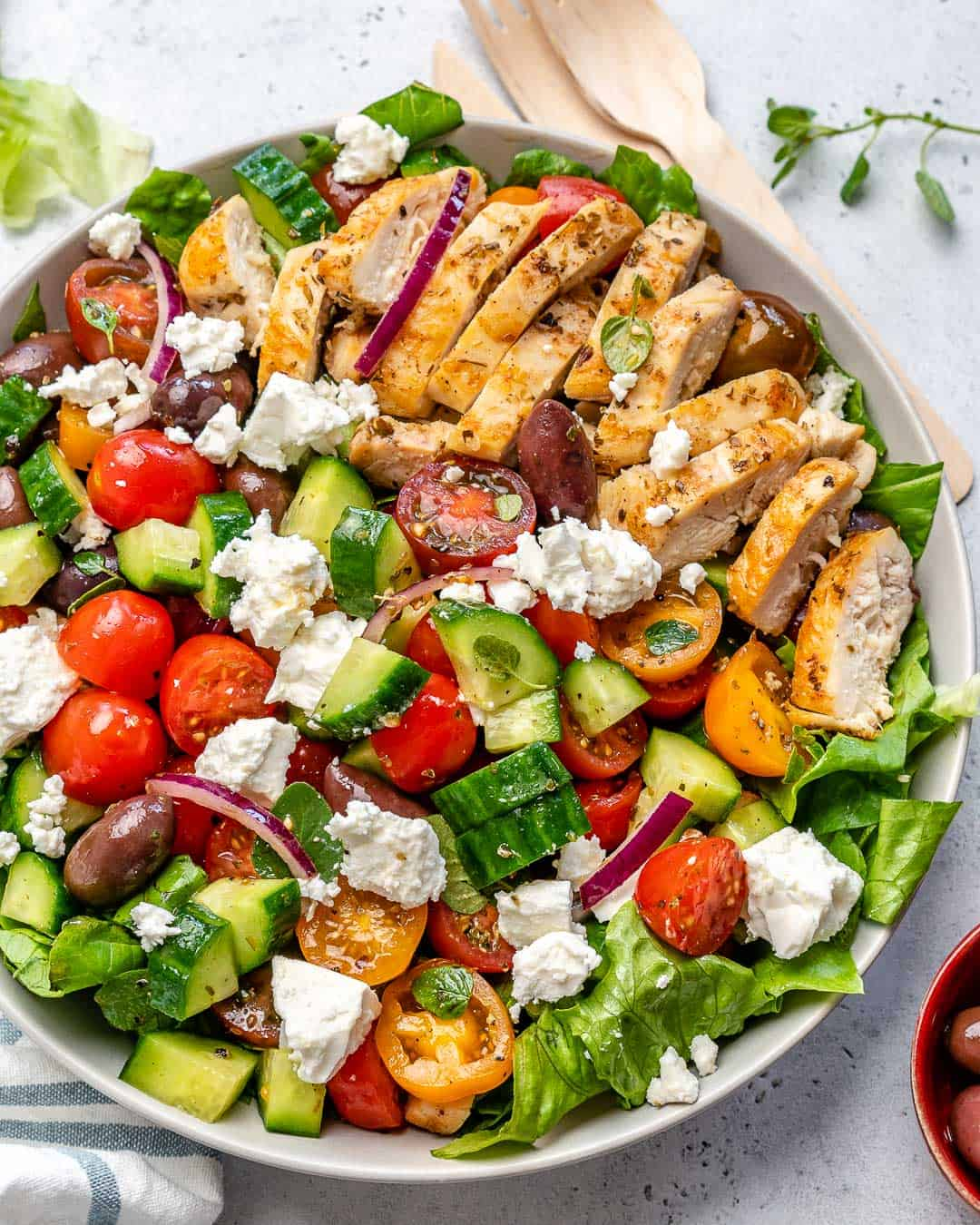 grilled chicken slices on salad in a white bowl