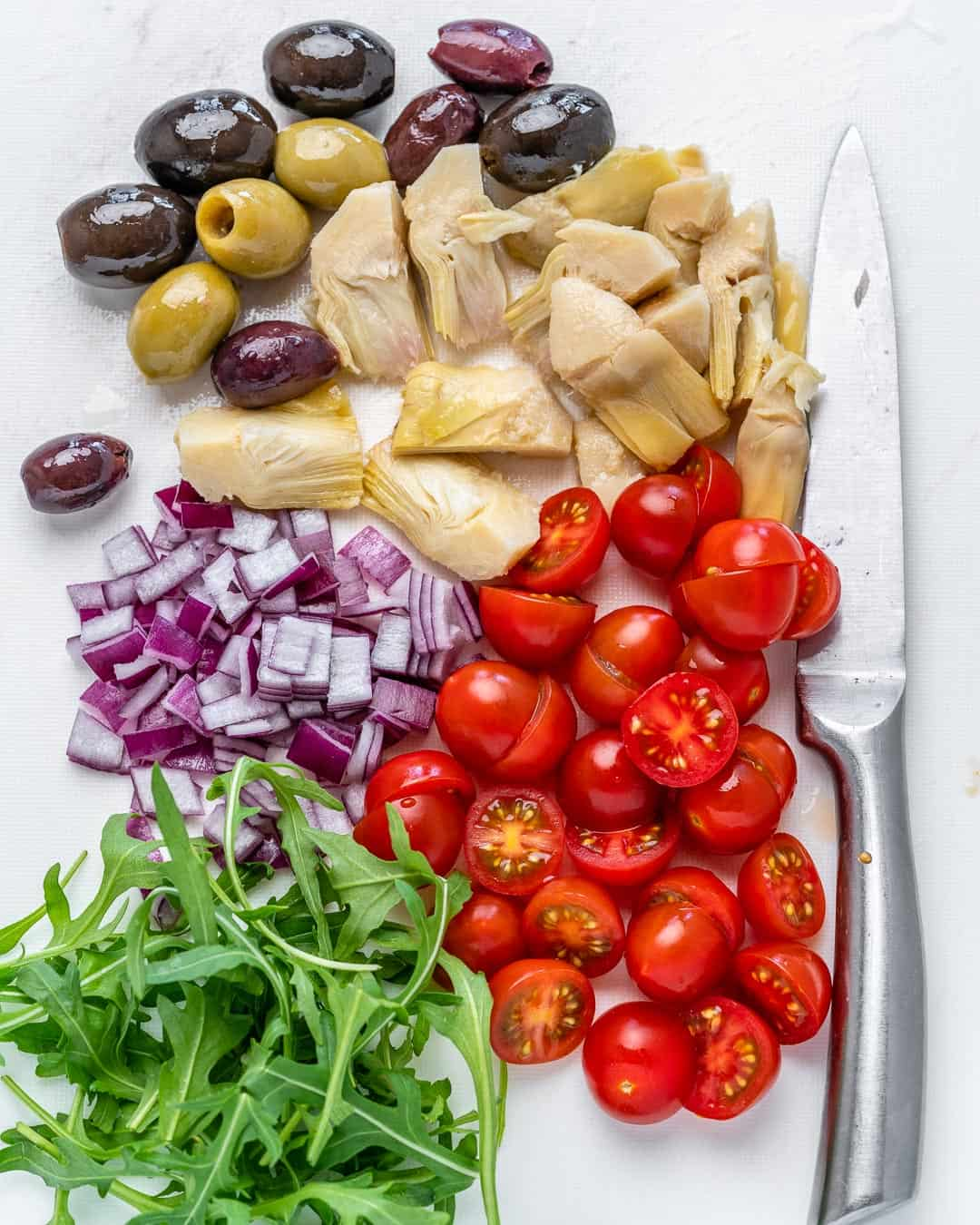 chopped pasta salad ingredients- tomatoes, onions, arugula, olives, and pickled artichoke