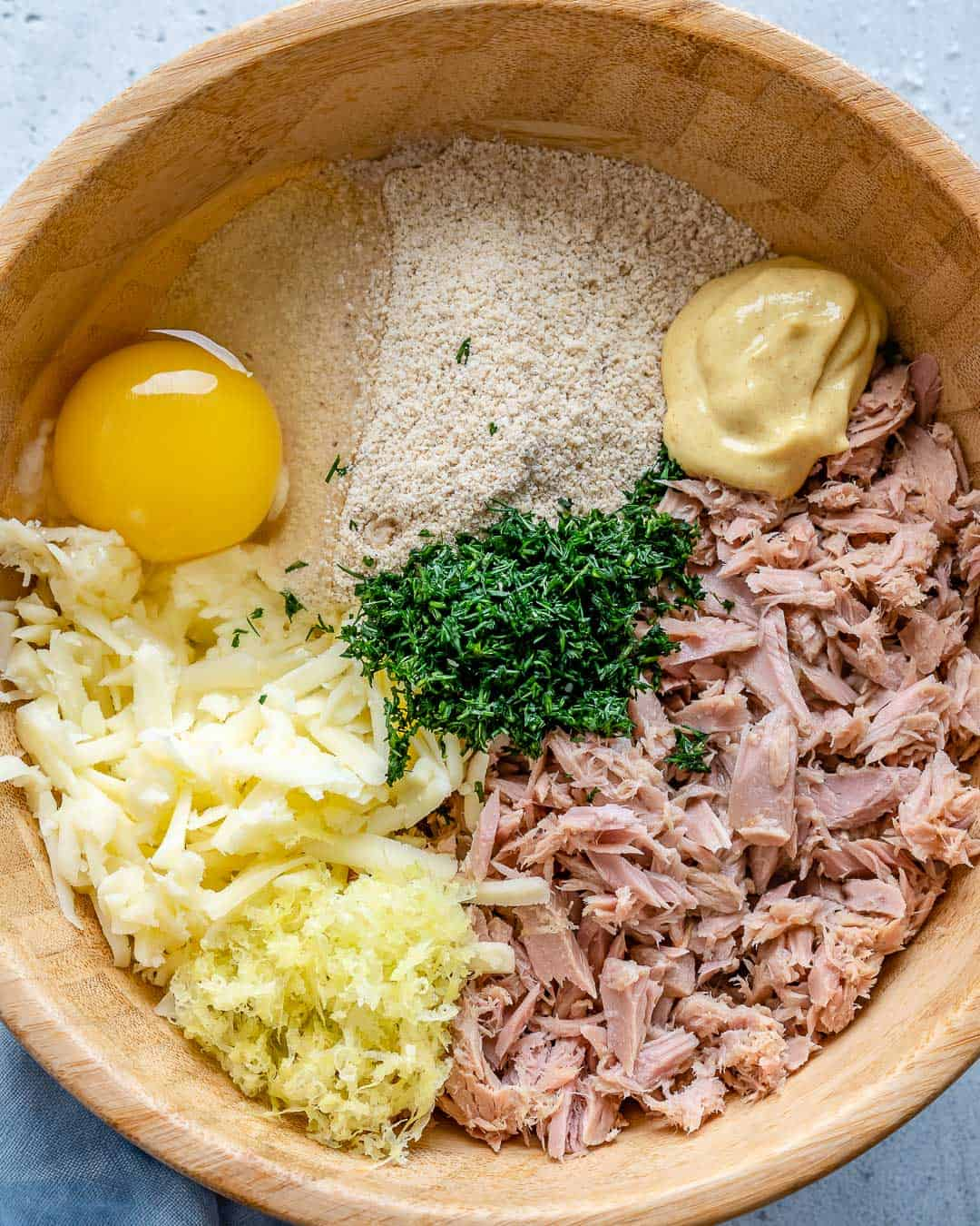 ingredients for the tuna patties in a brown bowl, egg, lemon zest, almond flour, mozzarella cheese, tuna, dill, and mustard.