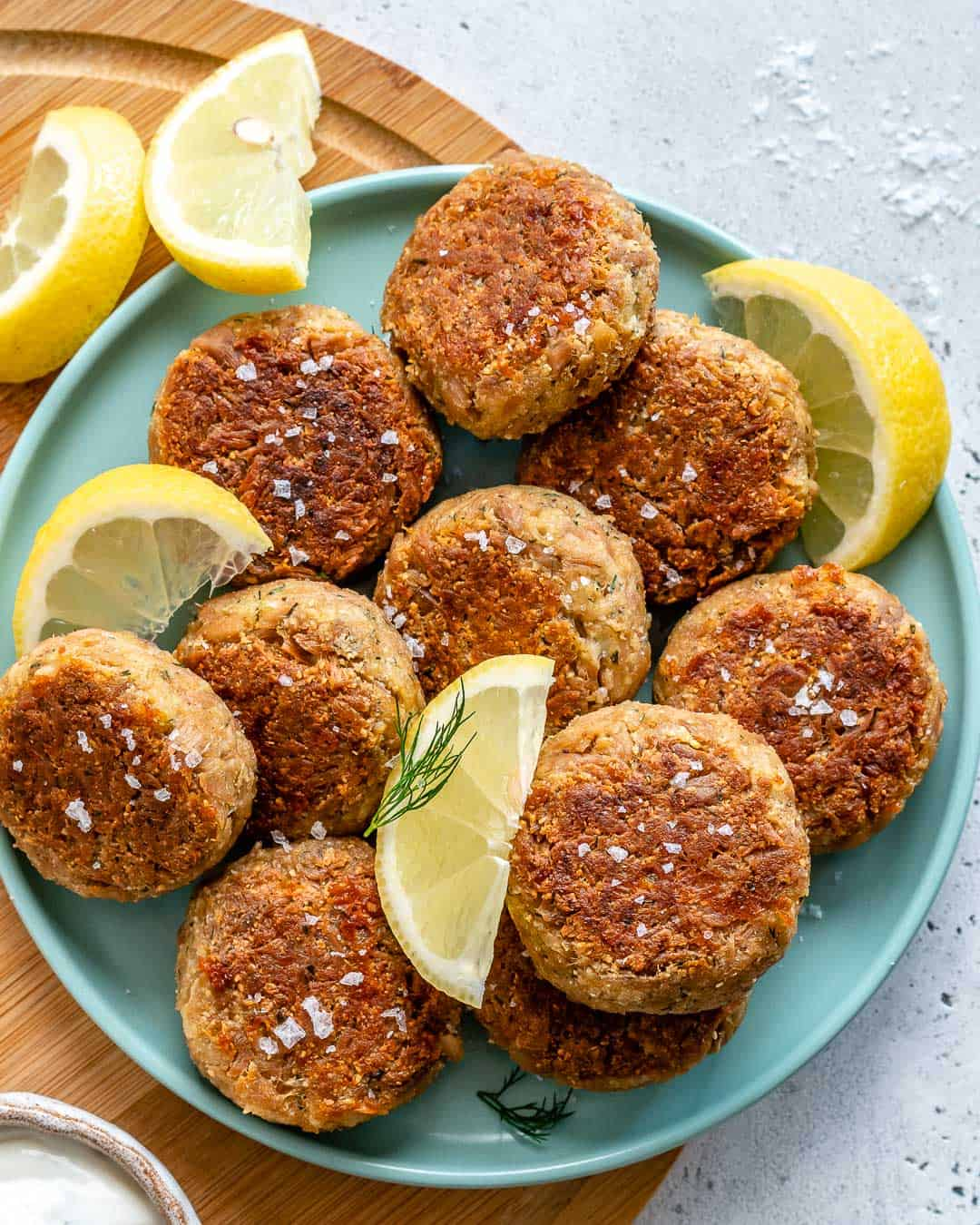 tuna cakes on a blue plate with lemon wedges as garnishes