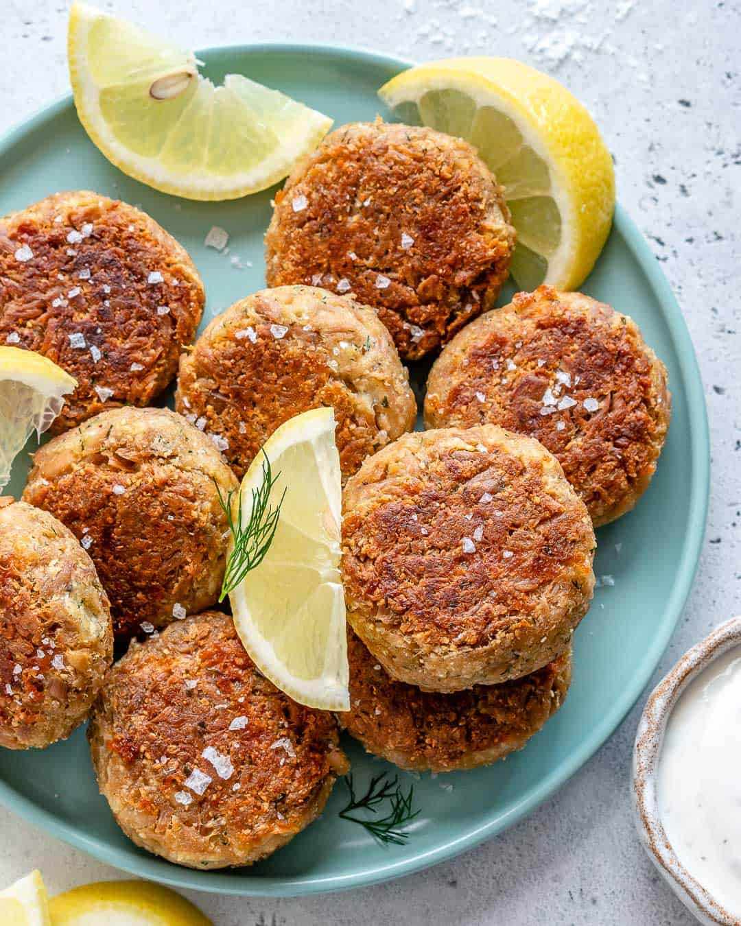 tuna patties on a plate with dill and lemon wedges garnishes