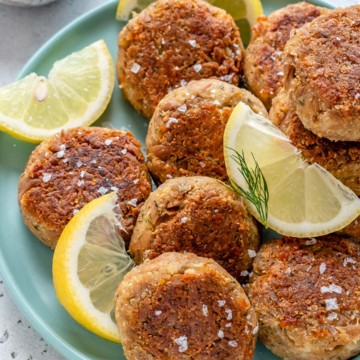tuna patties on a blue plate with lemon wedges