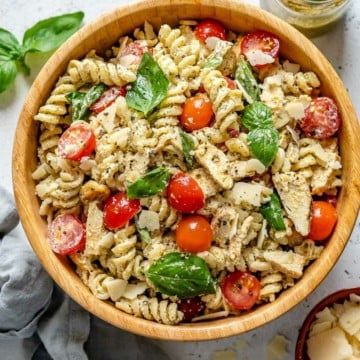 top view of pesto pasta with tomatoes, chicken, basil garnish