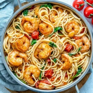 top view of shrimp and spaghetti in pan with tomato and spinach