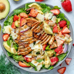 top view salad bowl with grilled chicken, strawberries, avocado, and cheese