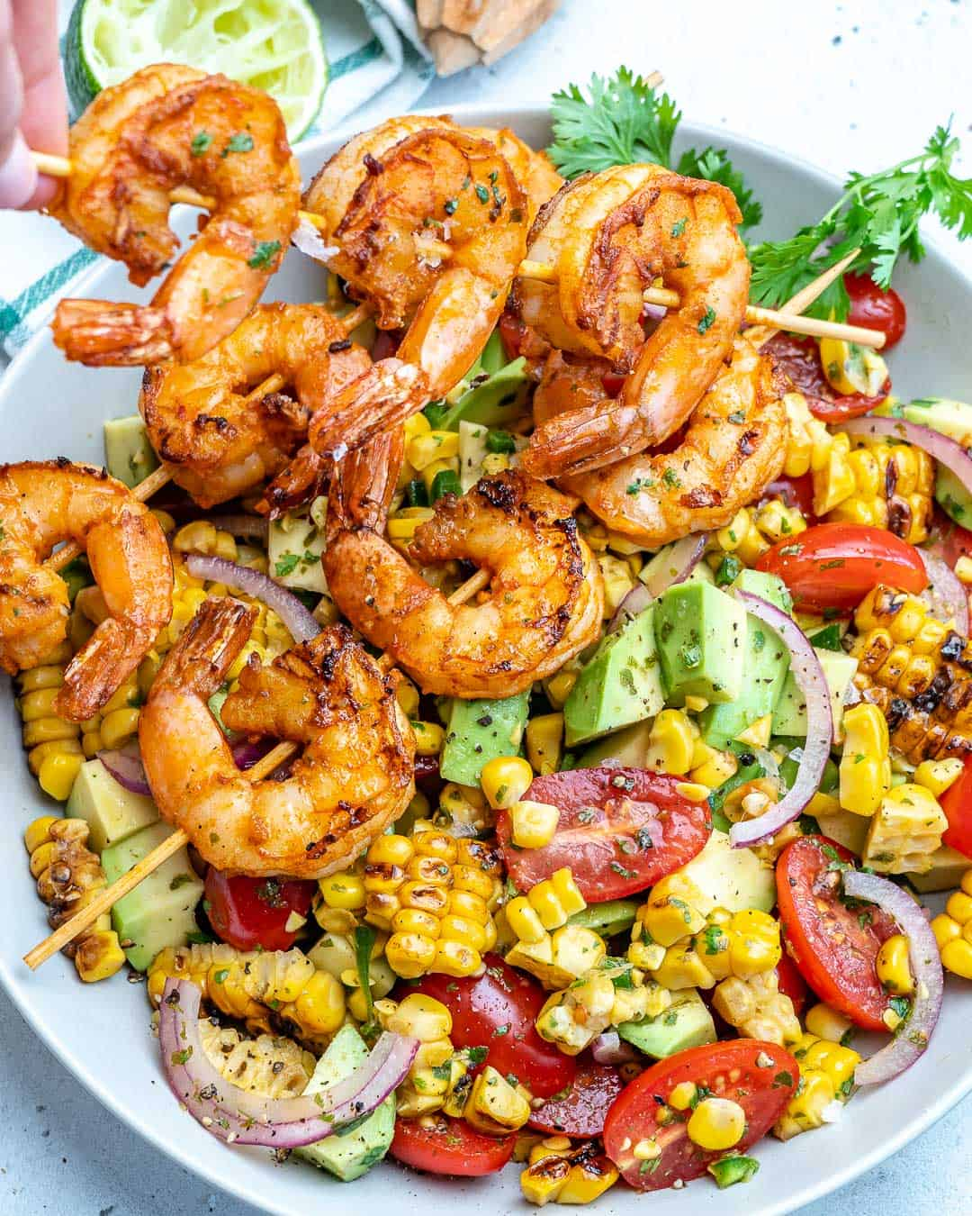 holding shrimp skewer over corn salad