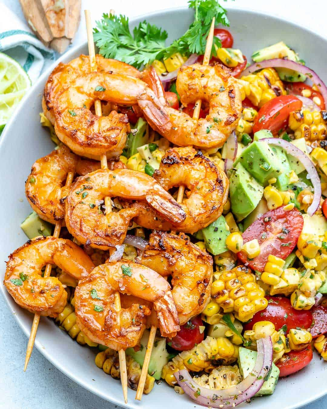 top view of corn salad with grilled shrimp skewers