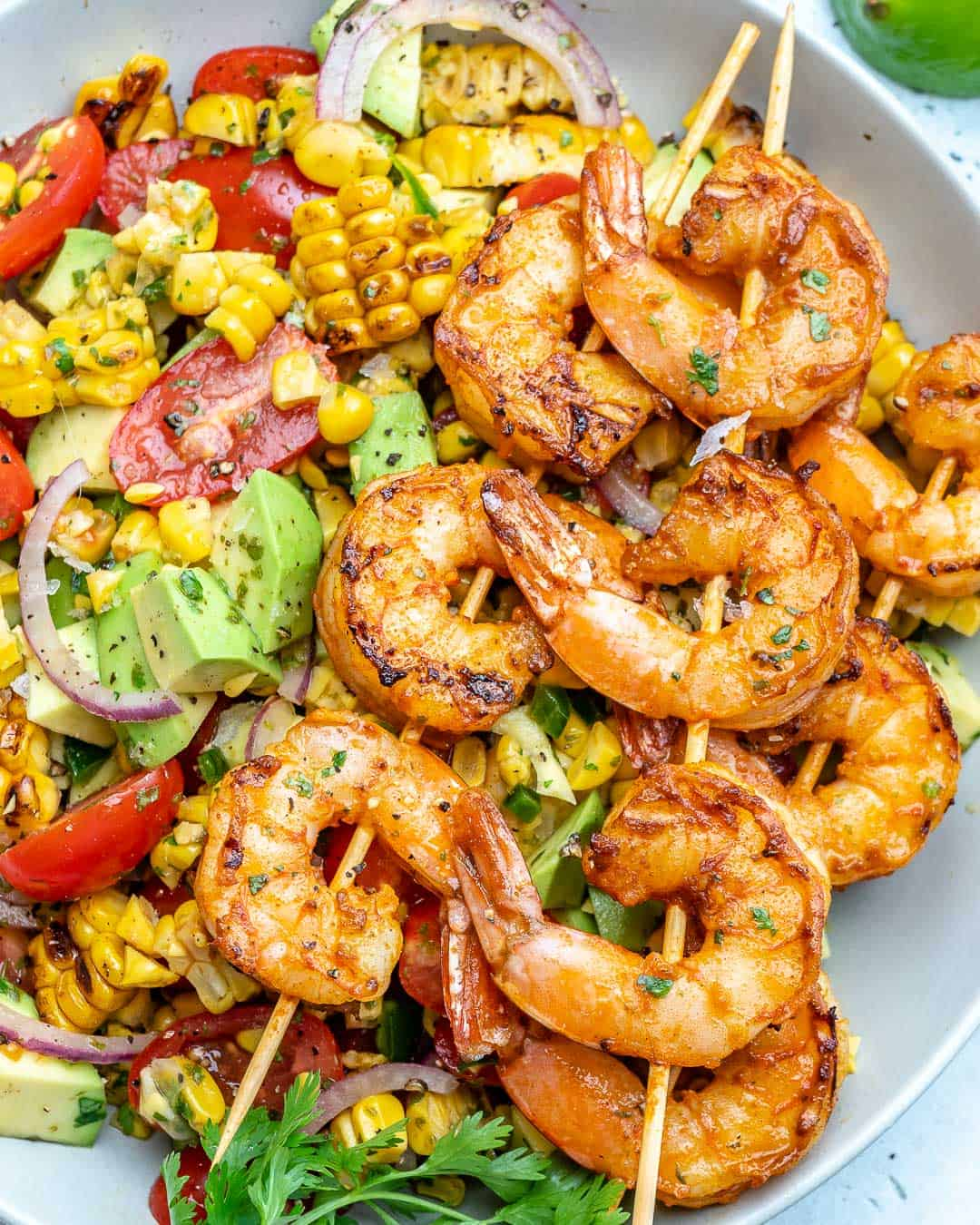 corn salad in a white bowl topped with grilled shrimp