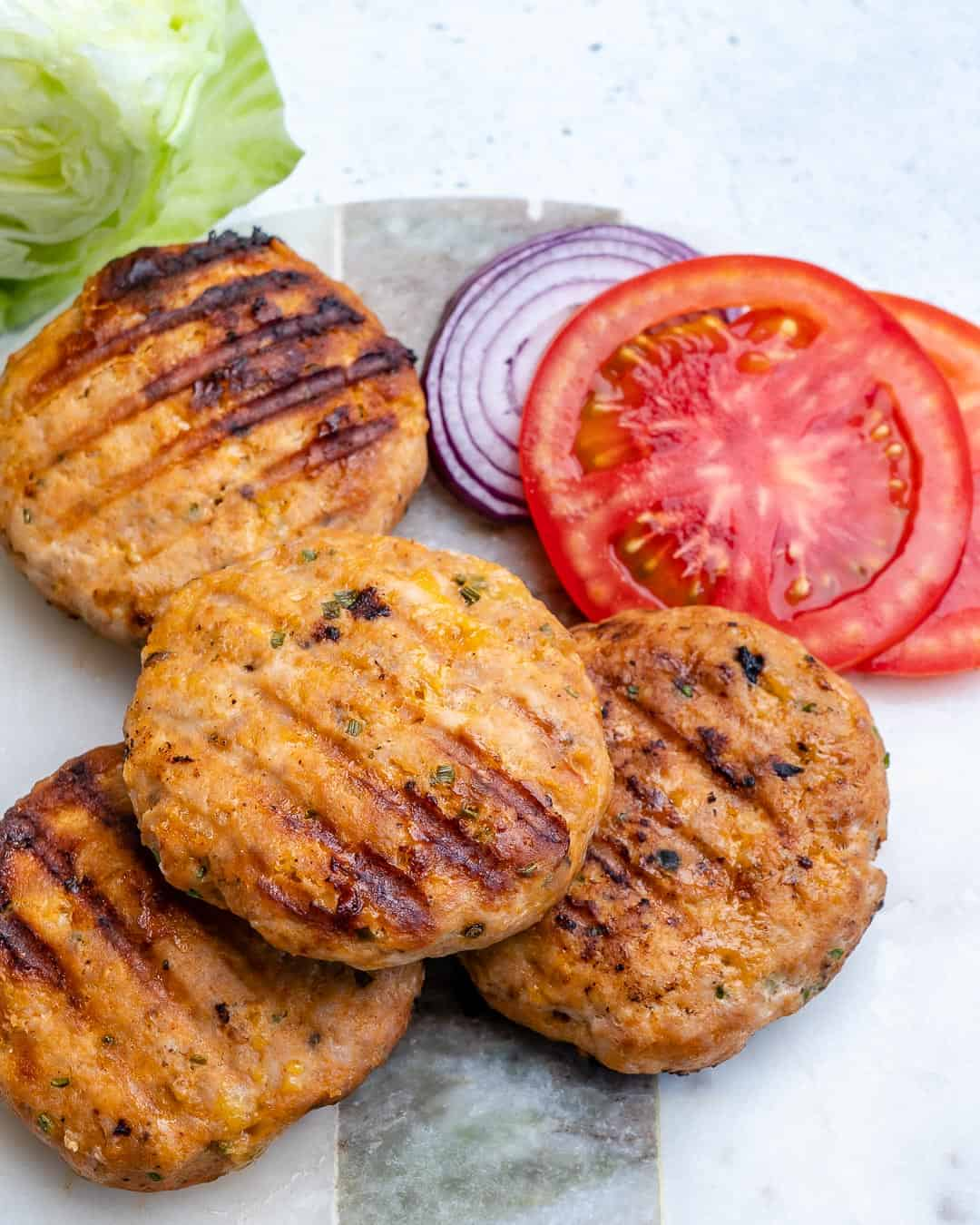 chicken burger patties on a cutting board with sliced tomatoes and onions on the side