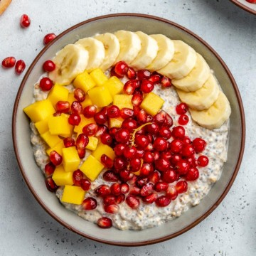 top view of oatmeal in a bowl with banana mango and pomegranate toppings
