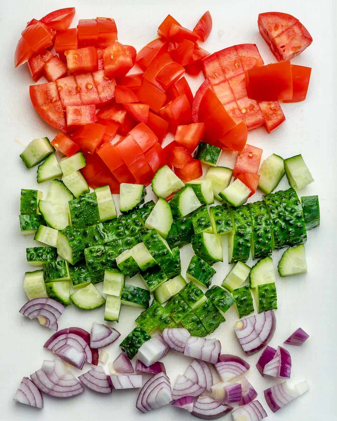 chopped onion, cucumber, and tomatoes on a white board