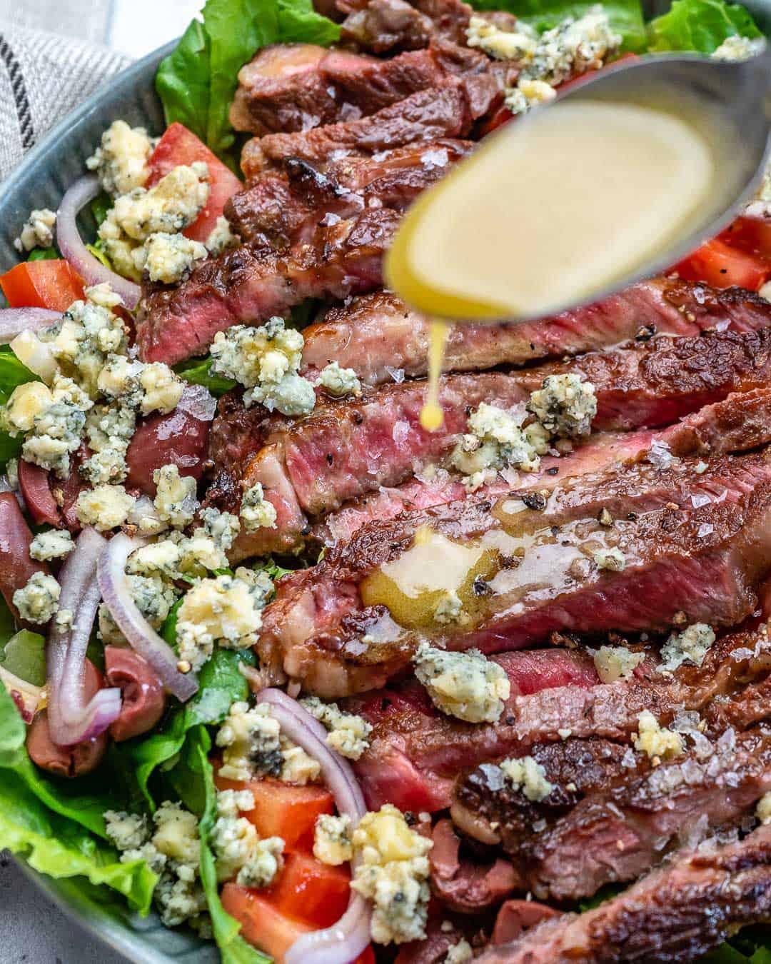 spooning dressing on Steak Salad Recipe