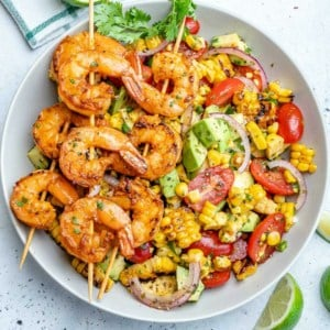 top view of corn salad with 3 skewers of grilled shrimp over salad