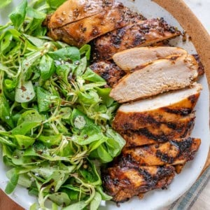 side view of sliced balsamic chicken breast with side green salad