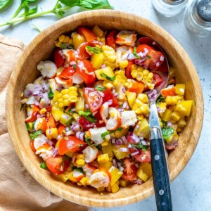 corn tomato and crab salad in a light brown bowl