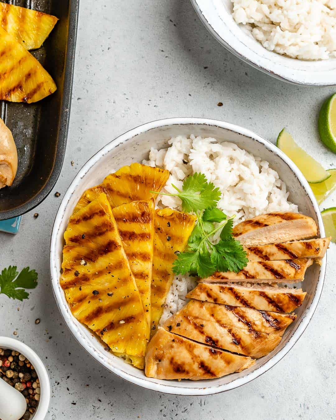 top view grilled pineapple and chicken breast over a rice bowl