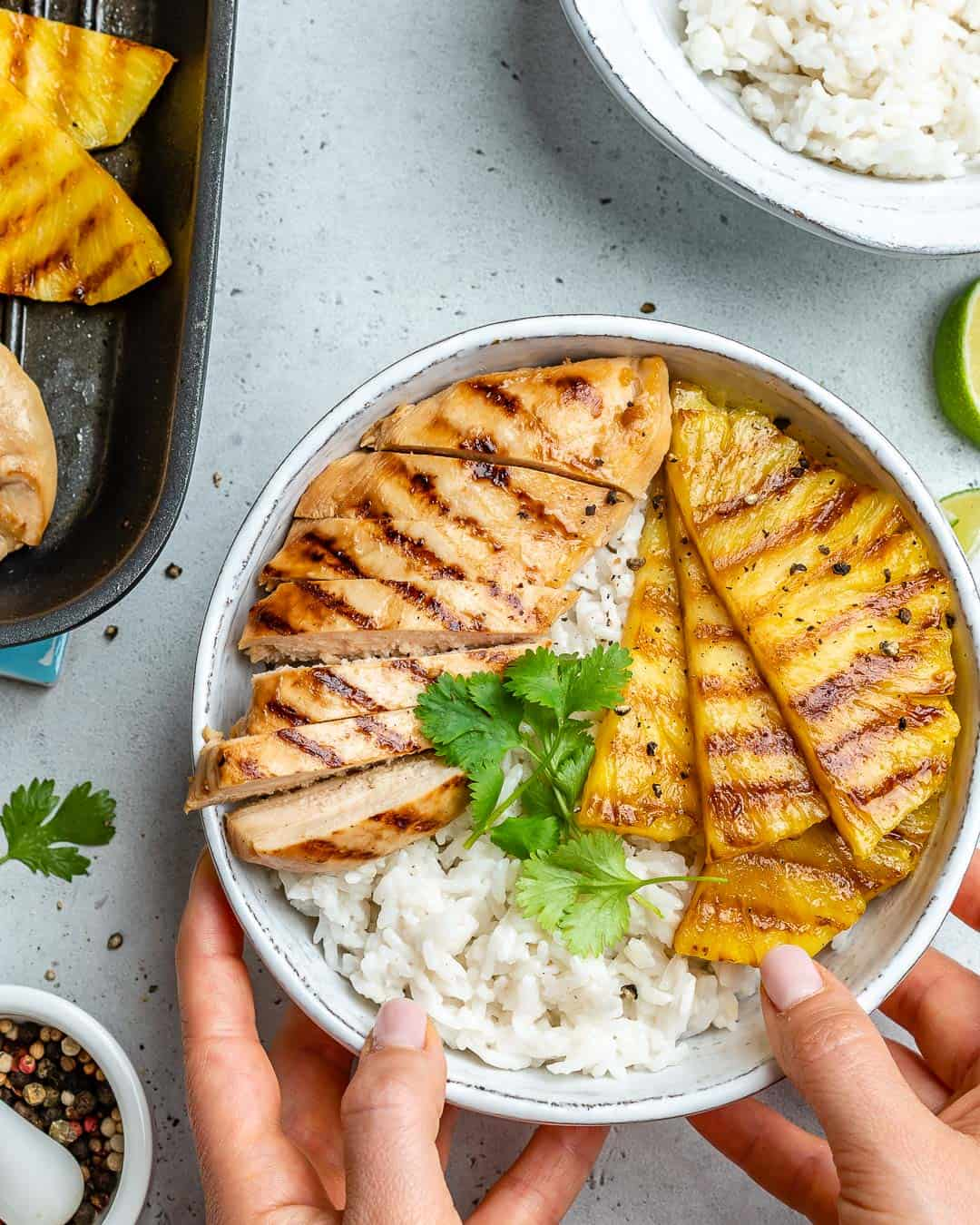 hand holding bowl of grilled chicken and rice