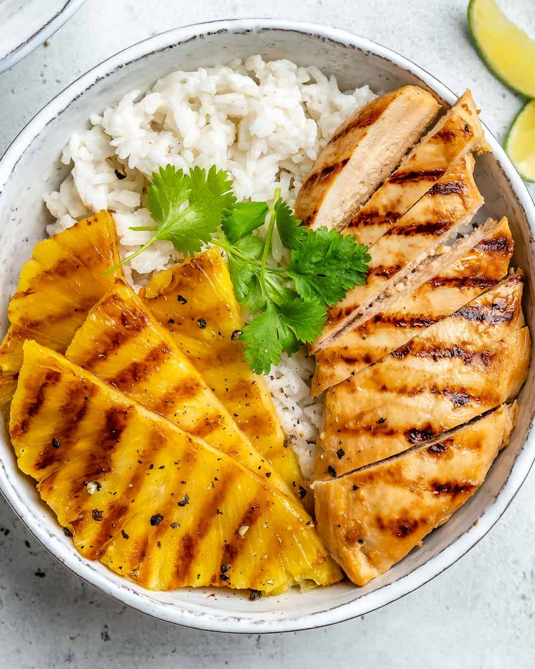 top view hawaiian chicken with grilled pineapple and coconut rice in a bowl