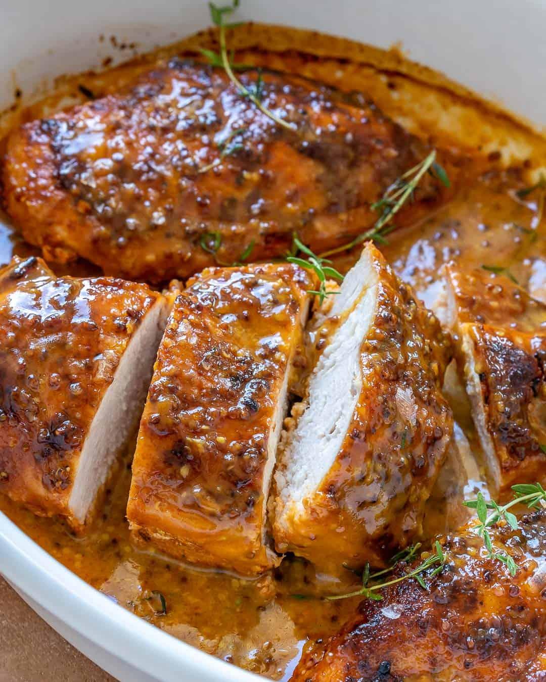 sliced mustard chicken breast in a baking dish