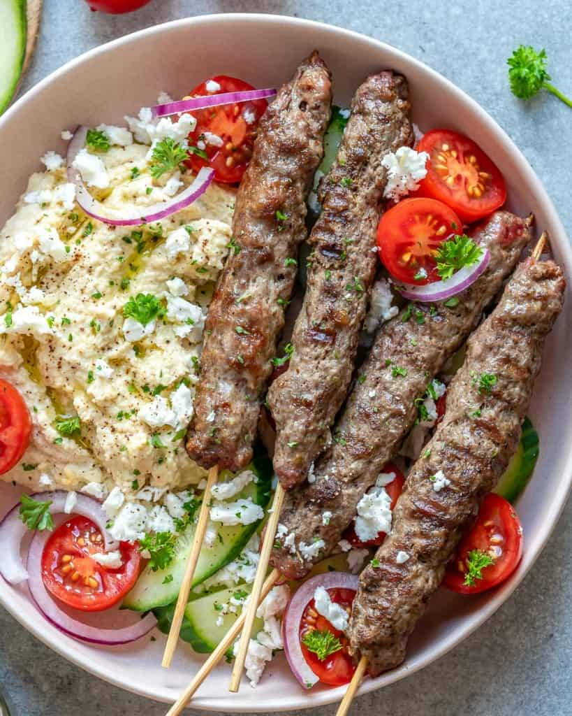 top view of 4 skewers of kafta on a plate with hummus