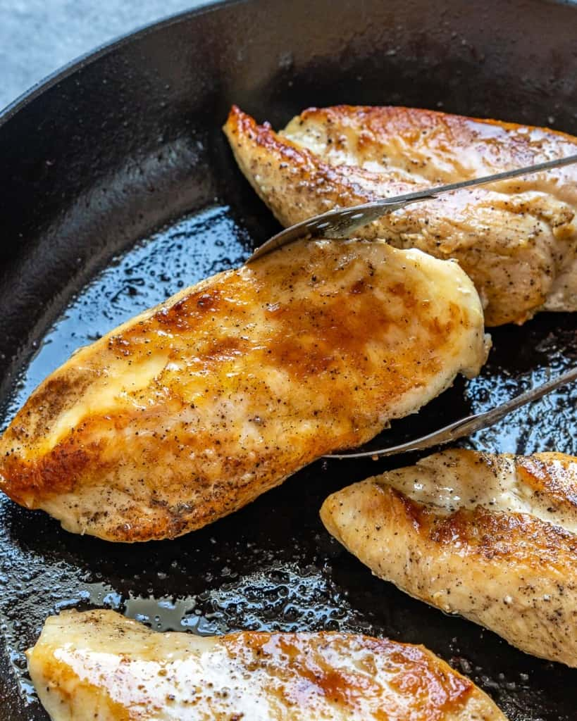 tongs grabbing a cooked chicken breast from skillet