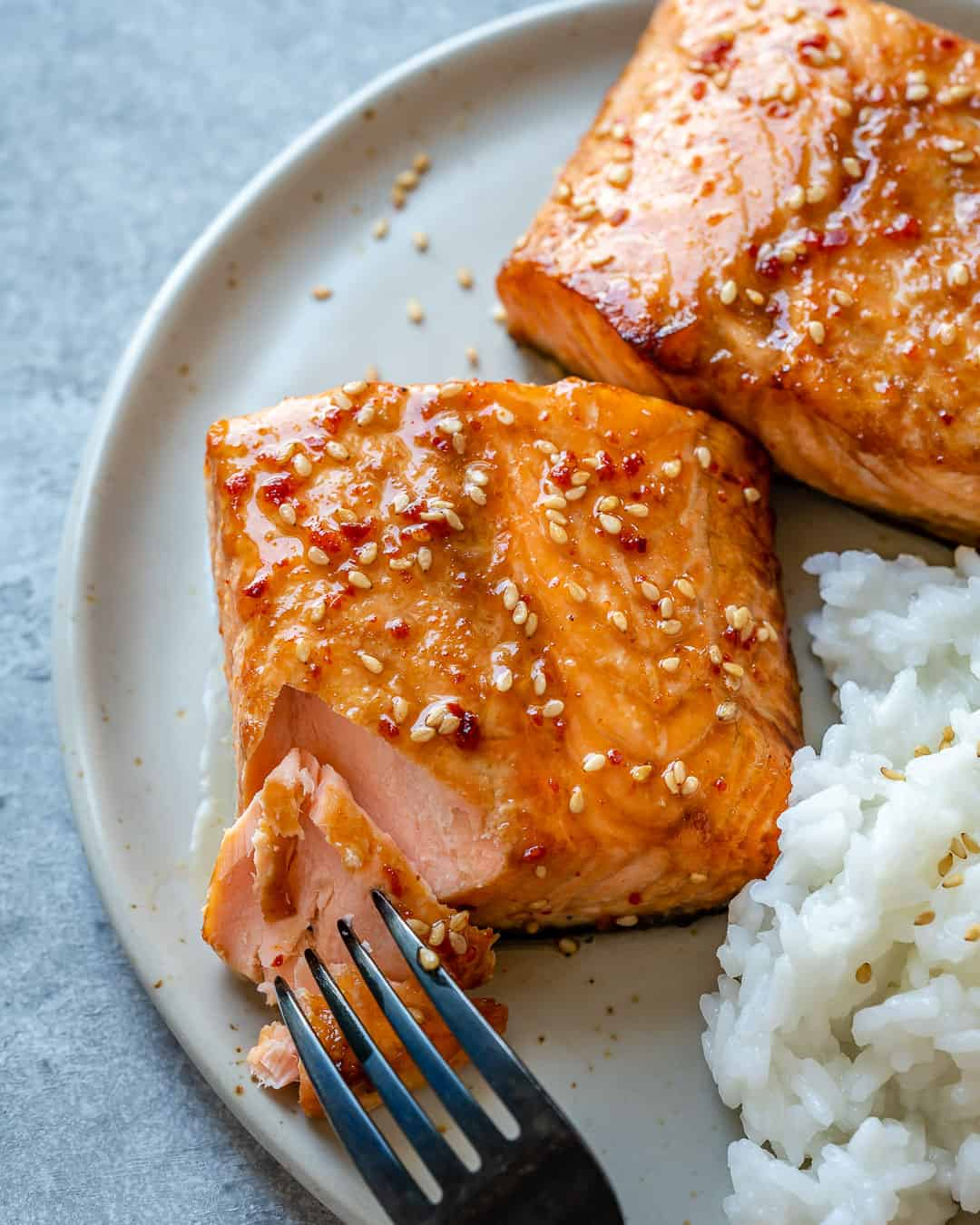 Fork with tender piece of honey glazed air fryer salmon