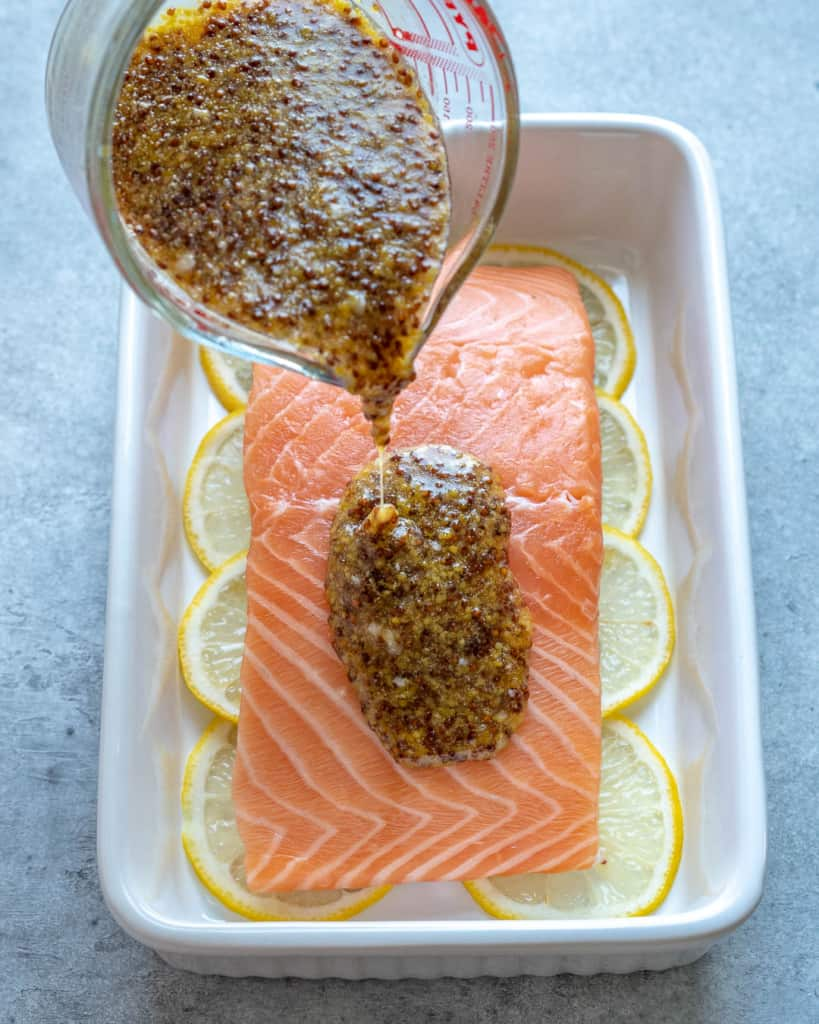 honey mustard marinade being poured over salmon