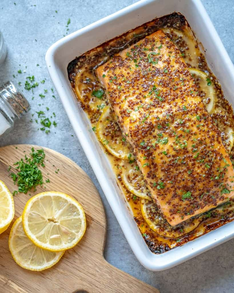 baked salmon in dish with lemon wedges on the left side