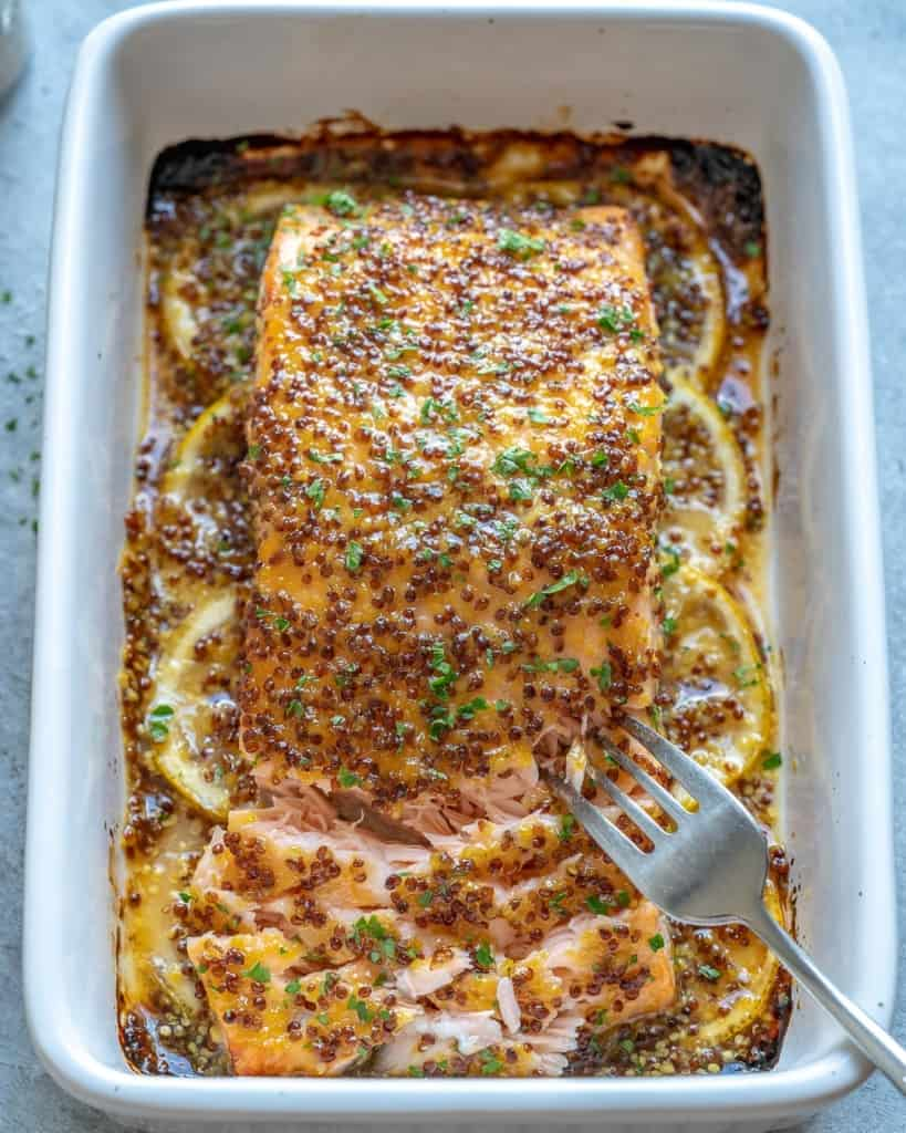 baked salmon in white dish with fork flaking it