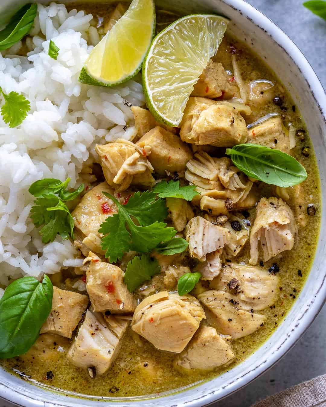Bowl of chicken curry with fresh toppings.